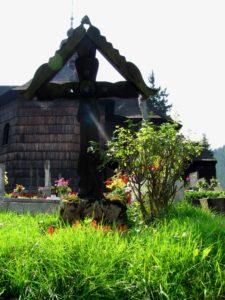 hrob na hřbitově ve Velkých Karlovicích, v pozadí dřevěný kostel Panny Marie Sněžné